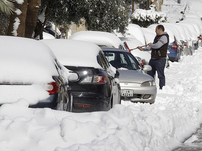 A man cleans snow from a car following a snowstorm in the Jordanian capital Amman on February 20, 2015. Blizzards dumped a blanket of snow over Israel, Jordan and Lebanon, with many residents urged to stay in their homes because of blocked or icy roads. (AFP photo)