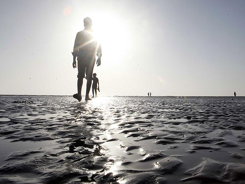 People take a stroll at Juhu beach as mercury levels continued to soar in Mumbai. (Vidya Subramanian/HT photo)