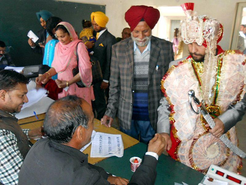A polling official marks the finger of a groom at a poling station for municipal corporation election in Pathankot. HT Photo