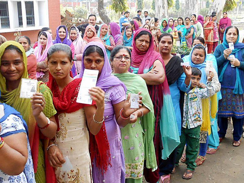 Voters stand in queue to cast their votes outside poling station for municipal corporation election in Pathankot. HT Photo