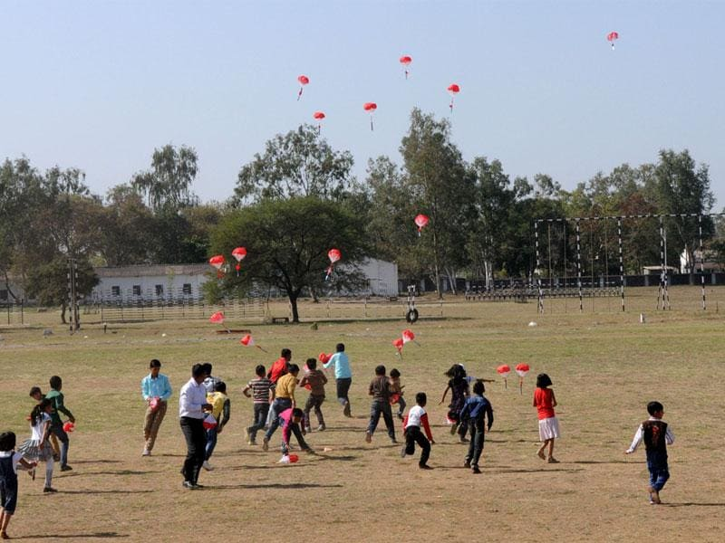 Children of Armymen try to catch chocolates dropped by a microlight aircraft of the Army expedition team during airshow in Bhopal on Sunday. (HT photo)
