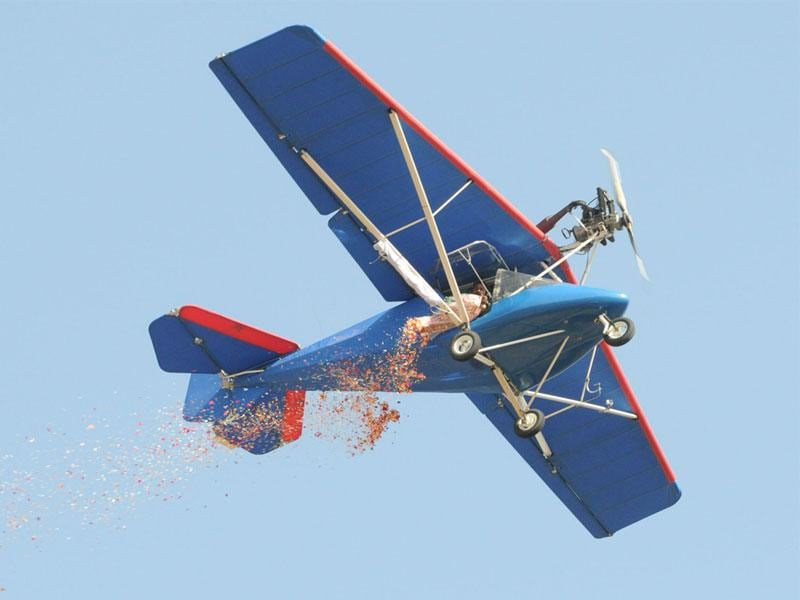A microlight aircraft of the army microlight expedition team showers flower petals during airshow in Bhopal on Sunday. (Mujeeb Faruqui/HT photo)