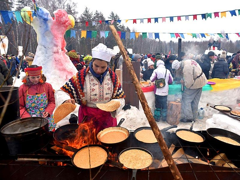 A woman prepares pancakes during celebration of Maslenitsa (Shrovetide), a farewell ceremony to winter close to village of Khlyupino about 60 km from Moscow. (AFP photo)
