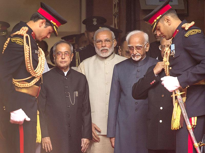 President Pranab Mukherjee (L), Prime Minister Narendra Modi, and vice-president Hamid Ansari (R) take their position during the start of a ceremonial procession to mark the beginning of the budget session in New Delhi. (AP Photo)