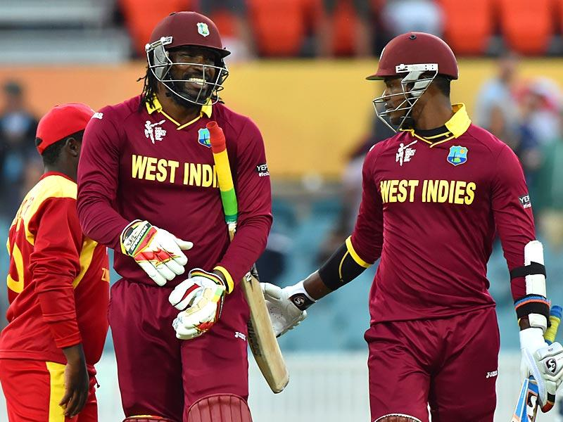 Chris Gayle (C) and teammate Marlon Samuels (R) celebrate at the end of their innings during the 2015 Cricket World Cup match between West Indies and Zimbabwe at Manuka Oval in Canberra. (AFP Photo)
