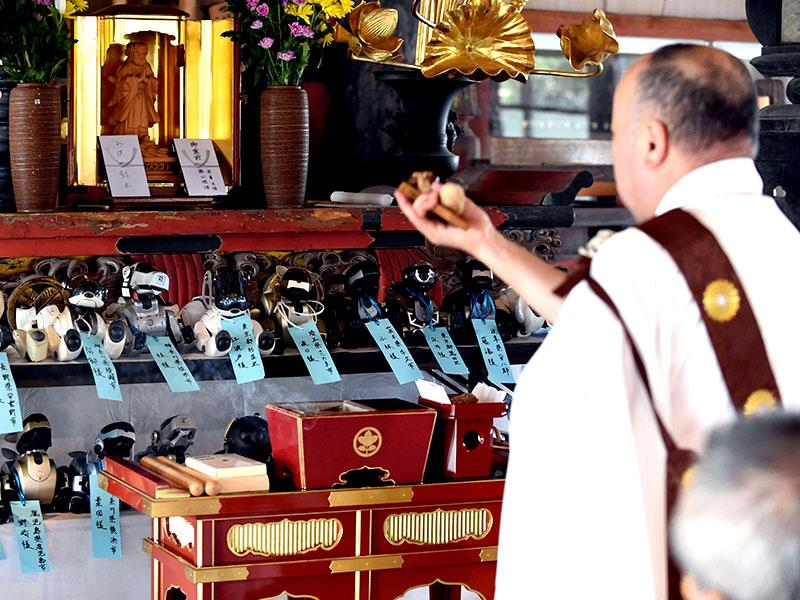 Kofuku-ji temple chief priest Bungen Oi (R) offers a prayer during the funeral for 19 Sony's pet robot AIBOs at the Kofuku-ji temple. (AFP PHOTO)