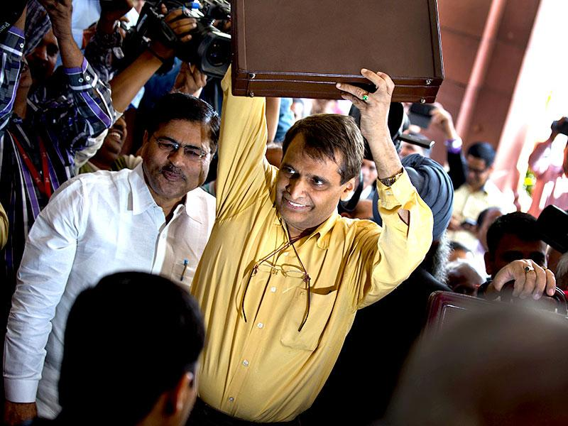 Railway minister Suresh Prabhu lifts the briefcase containing Railway budget for the year 2015-16 as he arrives at the parliament house to present it in New Delhi. (AP photo)