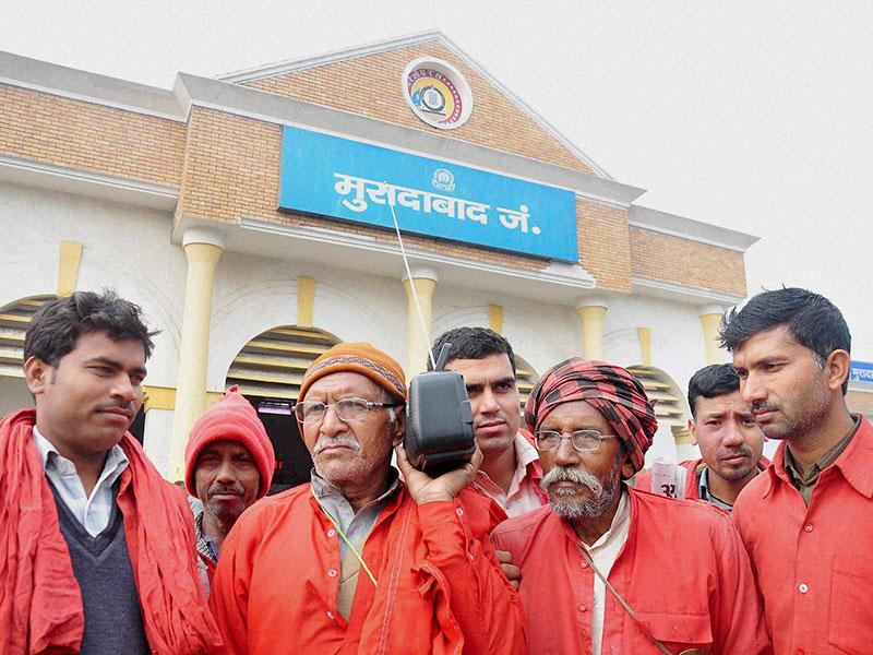 Porters listen to railway minister Suresh Prabhu's budget speech on a radio set in Moradabad. (PTI photo)