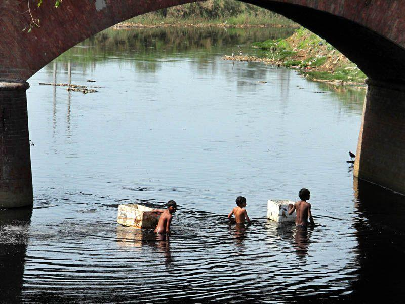 Unaware about the ill effects of the poisonous water mixed sewerage and chemical waste from the industries, children searching waste material in the Buddha Nullah.HT/Photo