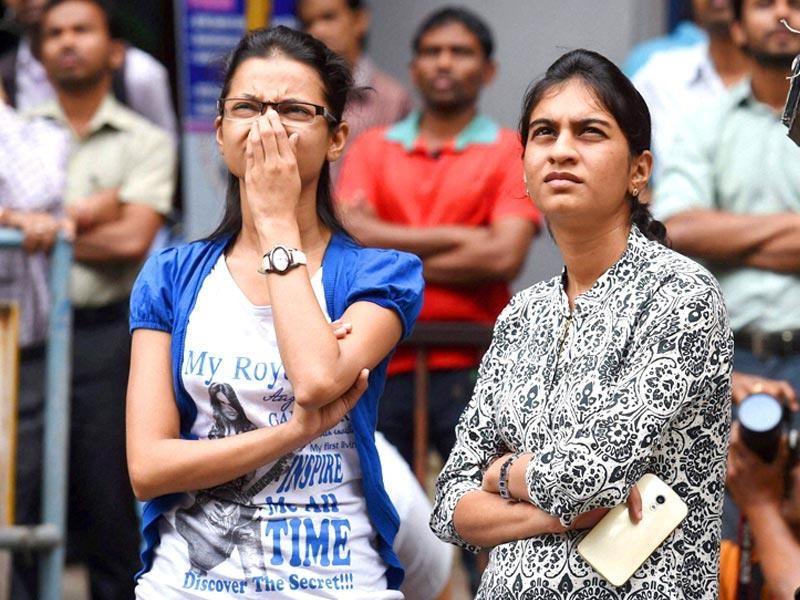 Onlookers watch the share prices on a display board at the BSE building in Mumbai during the Union budget 2015-16 presentation in the Lok Sabha. (PTI photo)