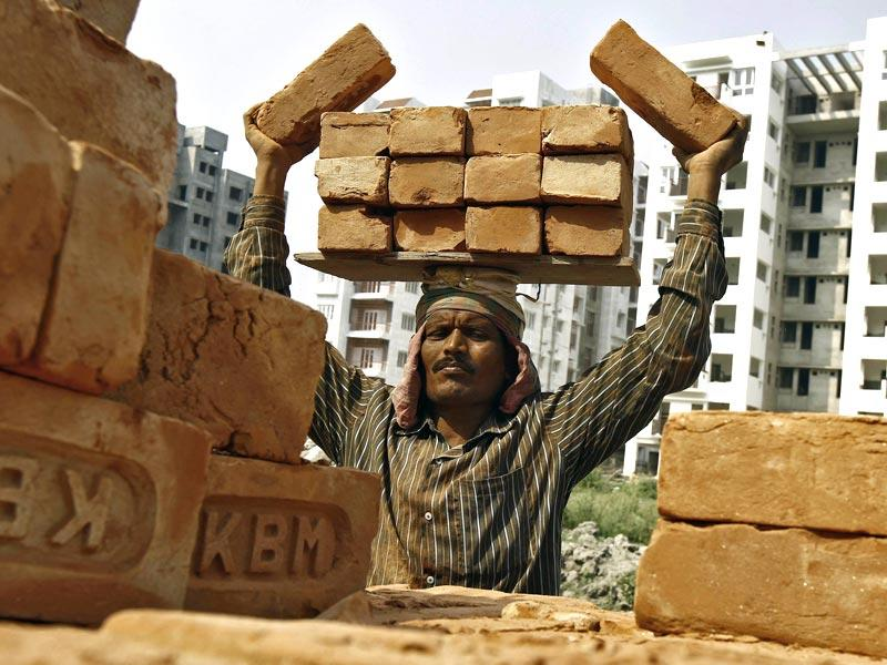 A labourer stacks bricks on his head at the construction site in Kolkata. FM Arun Jaitley announced a budget aimed at high growth, saying the pace of cutting the fiscal deficit would slow as he seeks to boost investment and ensure that ordinary people benefit. (Reuters photo)