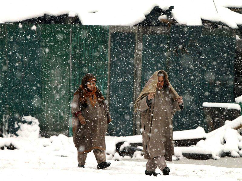 Kashmiri people walking in snow in Srinagar. Most parts of the Kashmir valley received fresh snowfall disrupting power supply, air and road traffic between Srinagar and Jammu. AP Photo