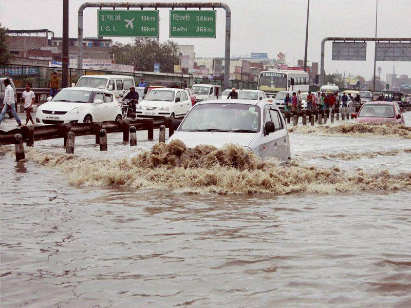 Vehicle moving through a water logged street at Hero Honda Chowk on Delhi-Gurgaon Expressway after heavy rains in Gurgaon on Monday. PTI Photo