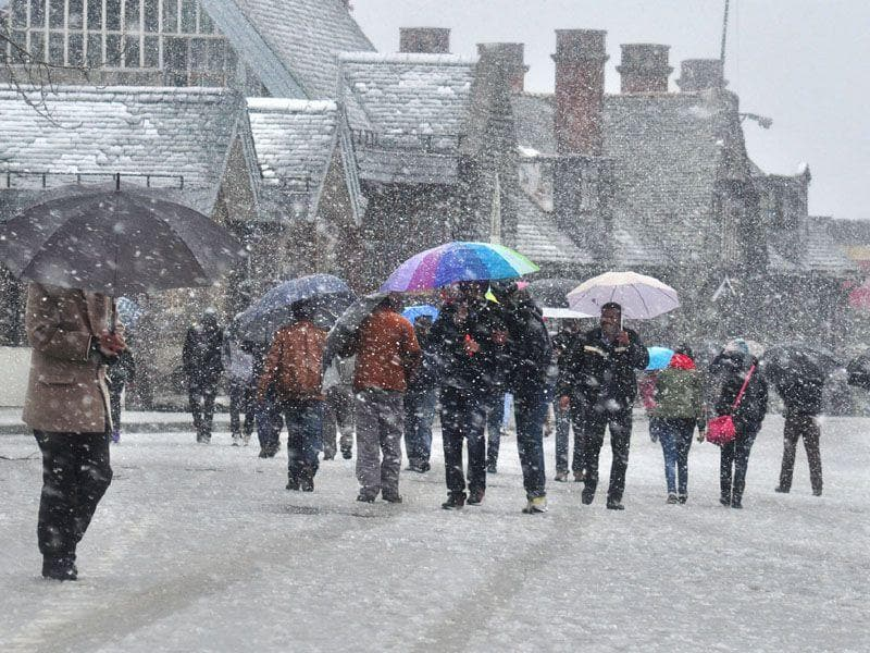 People walking during snowfall in Shimla. Temperatures remained below the freezing point at most places in Himachal Pradesh. Santosh Rawat/HT