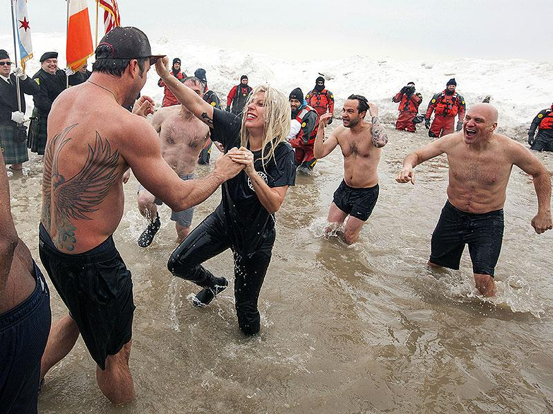 Actor Taylor Kinney, left, and his fiancée, pop star Lady Gaga, along with members of the Chicago Fire cast, take part in the Chicago Polar Plunge at North Avenue Beach. (AP)