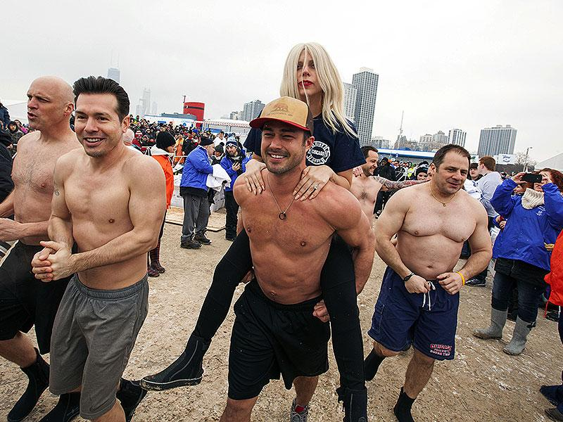 What happens when Lady Gaga jumps into freezing cold water? Too much cuteness! Gaga gets a piggy back ride from her fiancée, actor Taylor Kinney, after participating in the Chicago Polar Plunge. (AP)