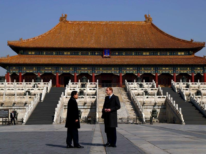 Britain's Prince William talks to a Chinese museum officer as he tours the Forbidden City during his first visit to Beijing . (AFP Photo)