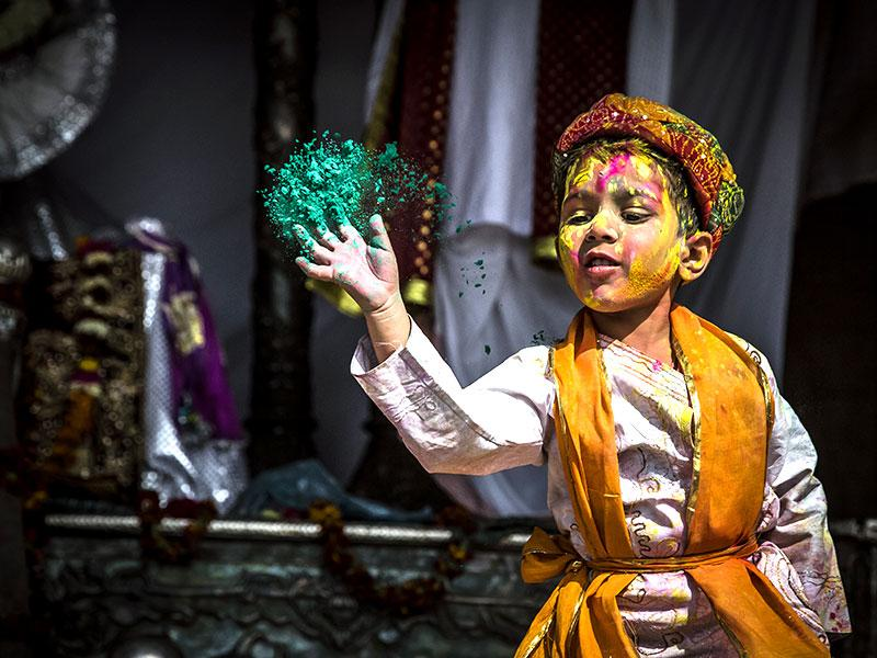 A child sprinkles colours on visiting pilgrims at Nandgaon temple. (Abhishek Saha/ HT Photo)