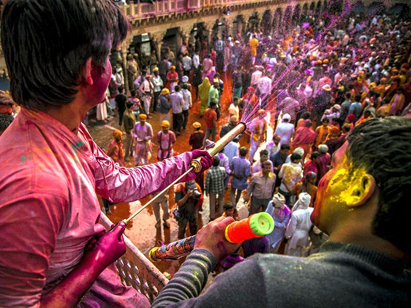 From the terrace of the Nandgaon temple, a man sprays coloured water on the gathering. (Abhishek Saha/HT Photo)