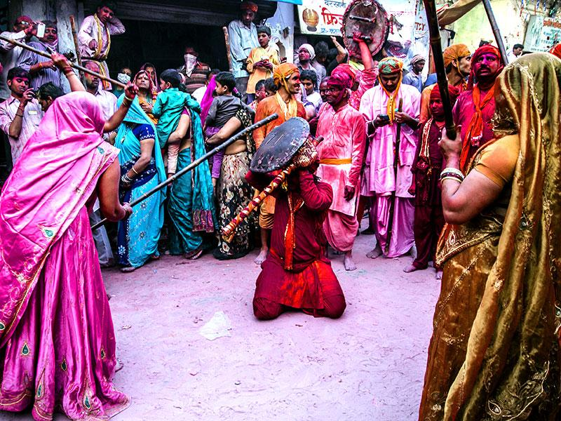 Barsana women mightily hit the shields of Nandgaon men, as Lathmaar Holi begins in Barsana. (Abhishek Saha/HT Photo)