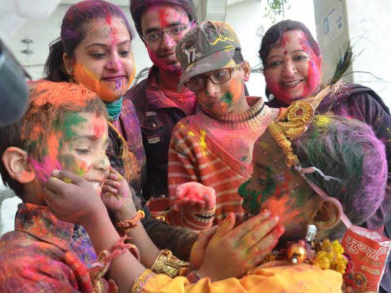 A child dressed as Lord Krishna plays with family members Holi at Durgiayana Temple in Amritsar. Sameer Sehgal/HT