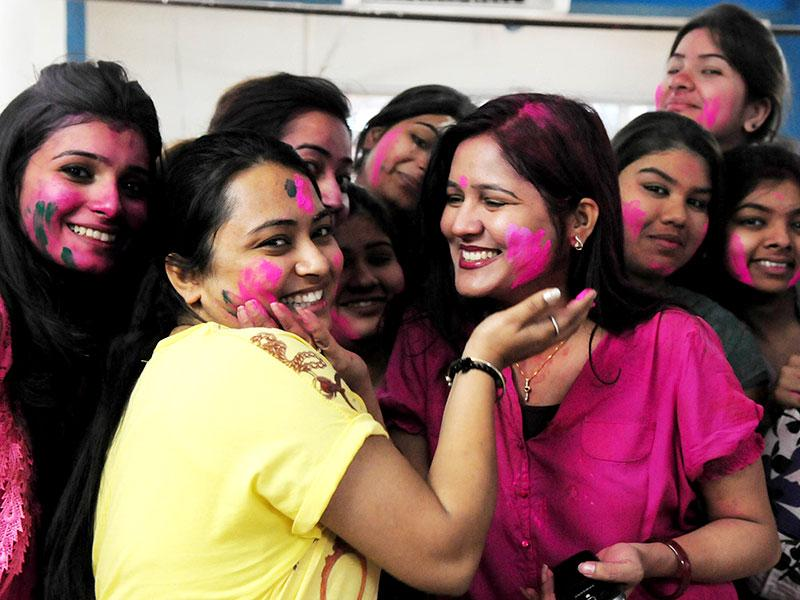 Young girls smear the faces of their friends with vibrant colors on the occasion of Holi, in Bhopal on Thursday. (Mujeeb Faruqui/HT photo)
