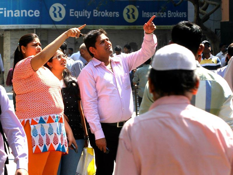 People look at the screen outside the Bombay Stock Exchange as the benchmark Sensex touched 30,000 mark in the early trading. (Arijit Sen/HT photo)