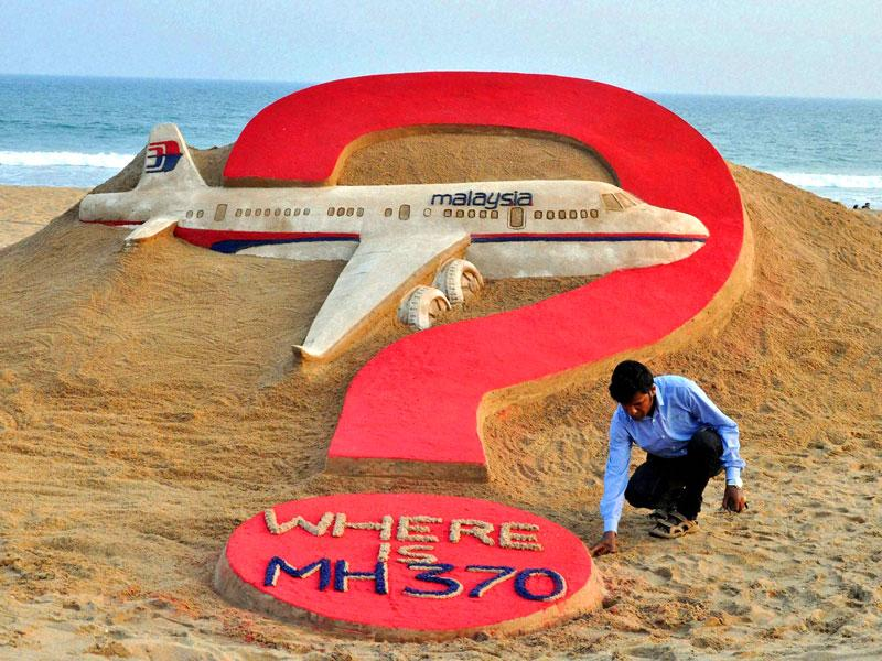 Sand artist sudarshan Pattnaik creates a sand sculpture in memory of the missing Malayasian flight in Puri on Saturday. (PTI Photo)