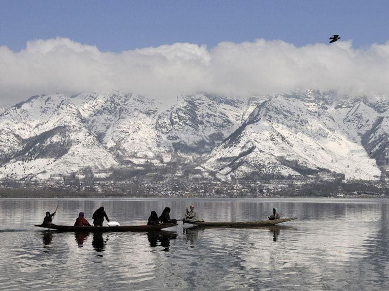 Kashmiri boatmen crosses the Dal Lake with the backdrop of snow covered mountains after a fresh snowfall in Srinagar. Waseem Andrabi/HT