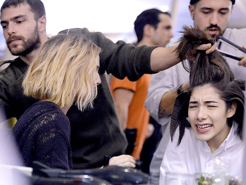 You've seen runway pictures, but what goes down backstage at Paris Fashion Week? Here are some revealing shots. Olympia Le Tan: Ouch! The hairstyling looks painful behind the scenes at the Olympia Le Tan show. (Photos: AFP)