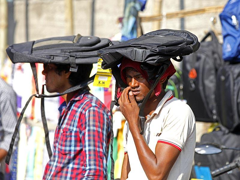Roadside vendors use school bags to beat the heat on a hot afternoon in Mumbai. (Pratham Gokhale/HT photo)