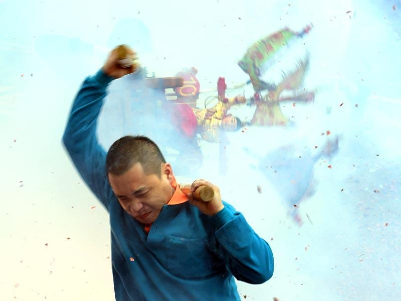 New Taipei City: A man carries a Taoist god statue as fire crackers are detonated during a lunar festival event at the Yehliu harbor in New Taipei City on March 5, 2015. More than 130 townspeople and tourists, plus a dog, threw themselves into Taiwan's northern Yehliu harbour carrying statues of a Taoist god in a centuries old tradition to pray for luck and prosperity for the year to come.