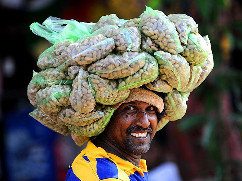 Colombo: A Sri Lankan fruit vendor waits to sell peanuts in Colombo on March 3, 2015. Sri Lanka's new government will seek loans exceeding 4.0 billion USD from international lenders, including the IMF, as it
