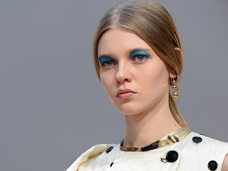 Celine: Color blocking was big news in Paris, where the makeup was bold, conceptual and theatrical. Céline put its stamp on the look with a vibrant stripe of primary blue over the eyelid.