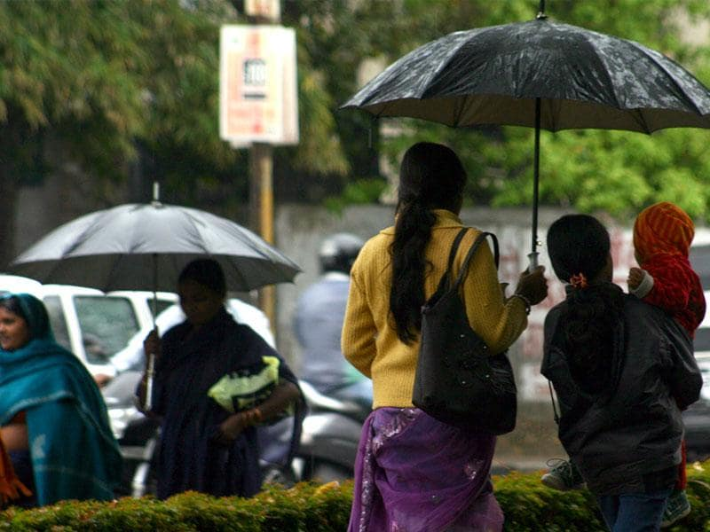 Moderate rains and cool breeze enveloped Bhopal on Friday, compelling people to take out their umbrellas and winter wear. (Bidesh Manna/HT photo)