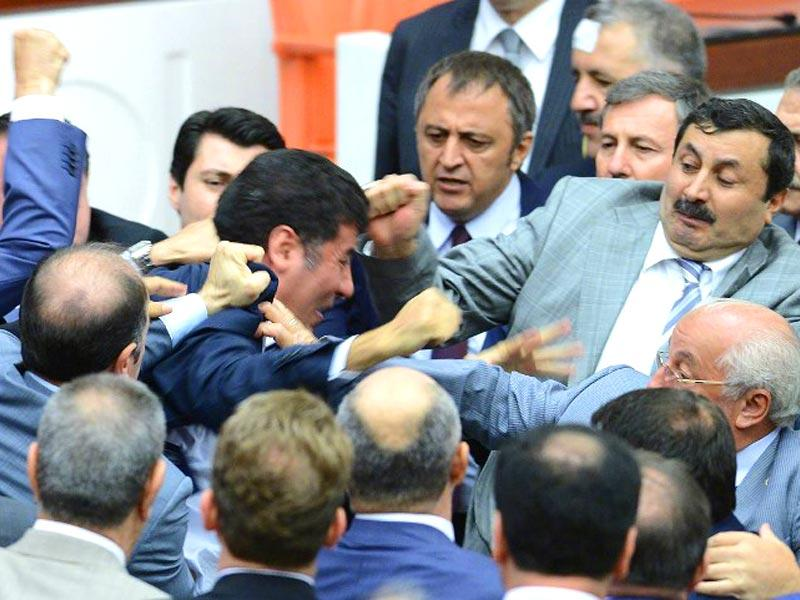 Opposition party MHP's deputy Sinan Ogan fights with colleagues at the parliament in Ankara, on August 4, 2014. Violent scuffles erupted in the Turkish parliament between opposition and ruling party lawmakers over the formation of a commission into the radical Islamist threat in neighbouring Iraq. (AFP Photo)