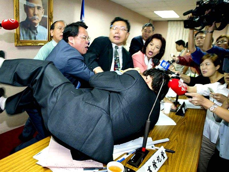 Chung Shao-ho (top-L), legislator from the opposition People First Party (PFP), fights with legislator Kuo Jung-chung (on table) from the ruling Democratic Progressive Party (DPP) before the start a Defense Committee meeting at the parliament building in Taipei, 06 November 2003. (AFP Photo)