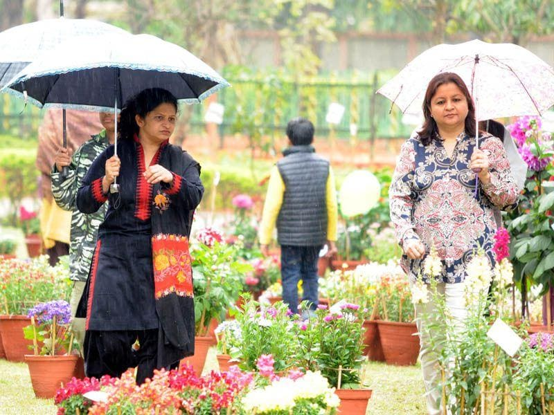 Ladies enjoying rain during flower show at Jawahar Garden in Jalandhar Cantt on Sunday. Pardeep Pandit/HT