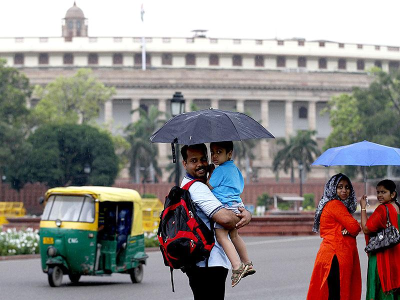 People taking shelter under umbrella during cloudy weather near Parliament house, in New Delhi. (HT Photo/Arvind Yadav)