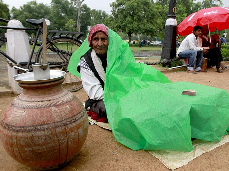 A roadside vendor protecting himself with plastic, during the rain in New Delhi, India. (HT Photo/Sanjeev Verma)