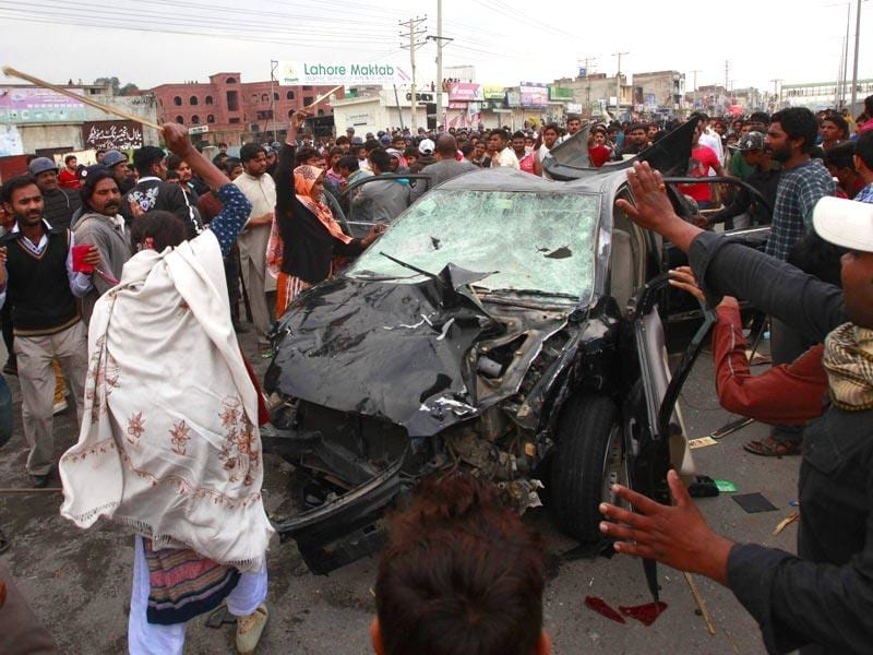 Protesters from the Christian community attack a car during clashes with riot police, a day after suicide attacks on two churches in Lahore. Reuters Photo