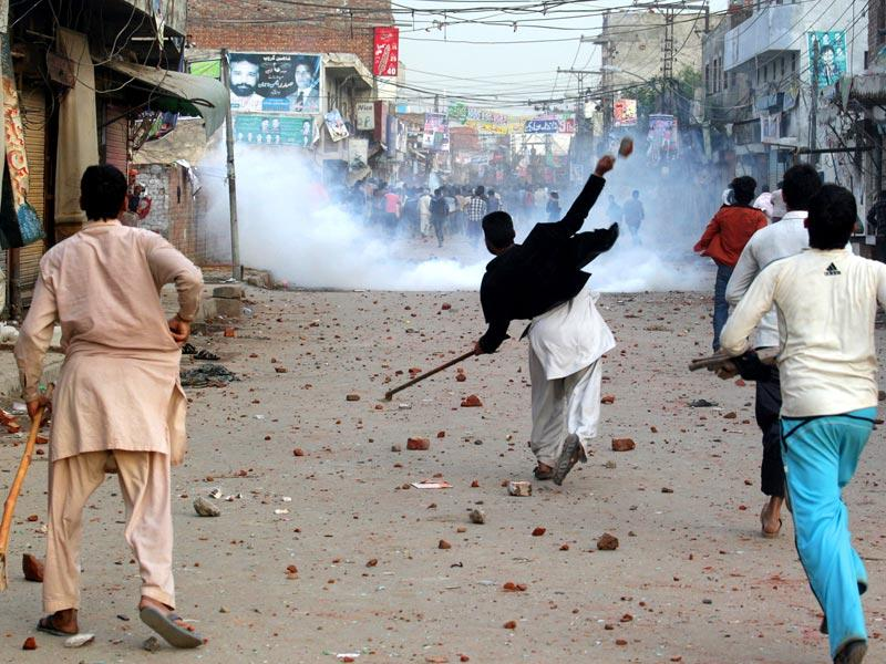 Pakistani protesters throw rocks during clashes with police to condemn suicide bombings that struck two churches in Lahore. AP Photo