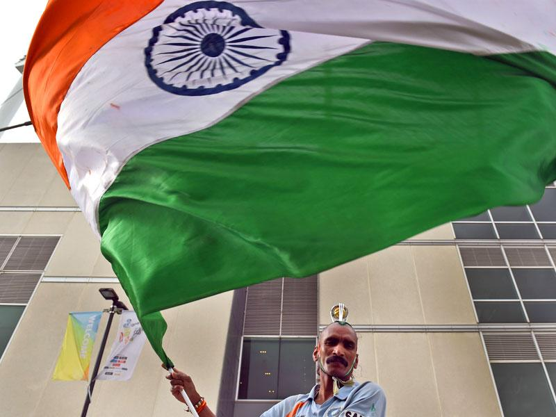 A fan waves the Indian national flag during the Indian cricket team's training session ahead of their 2015 Cricket World Cup quarter-final match against Bangladesh, in Melbourne on March 18, 2015. (AFP Photo)