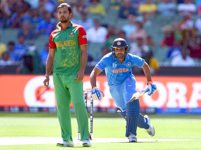 Rohit Sharma takes a run as Bangladesh bowler and captain Mashrafe Mortaza looks on during the 2015 World Cup quarter-final match between India and Bangladesh in Melbourne. (AFP Photo)