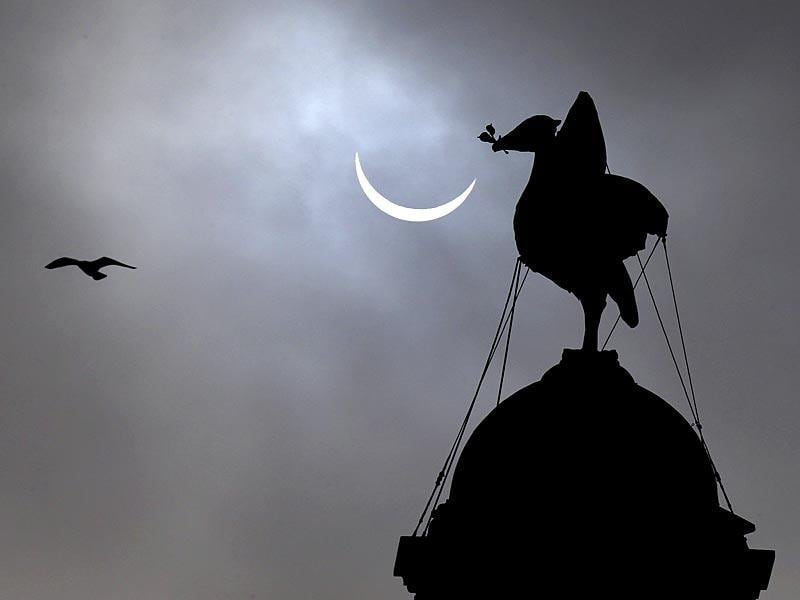 The sun is partially blocked by the moon during a solar eclipse seen over the Liver Building in Liverpool, England. (AP Photo)