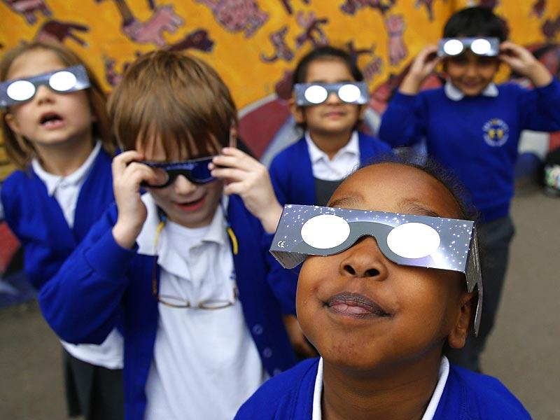 Children at a school wear solar viewing glasses as they try to see a partial solar eclipse in London. (Reuters)