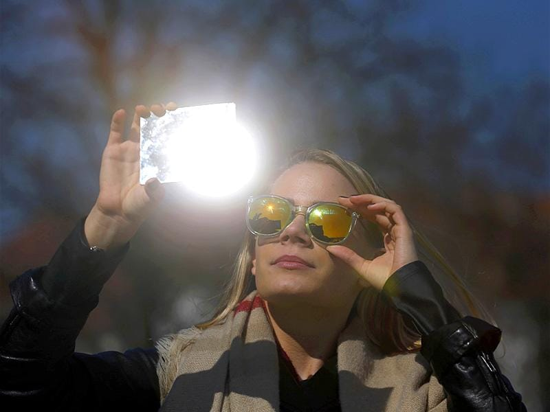 A woman watches a partial solar eclipse in Budapest. (Reuters)
