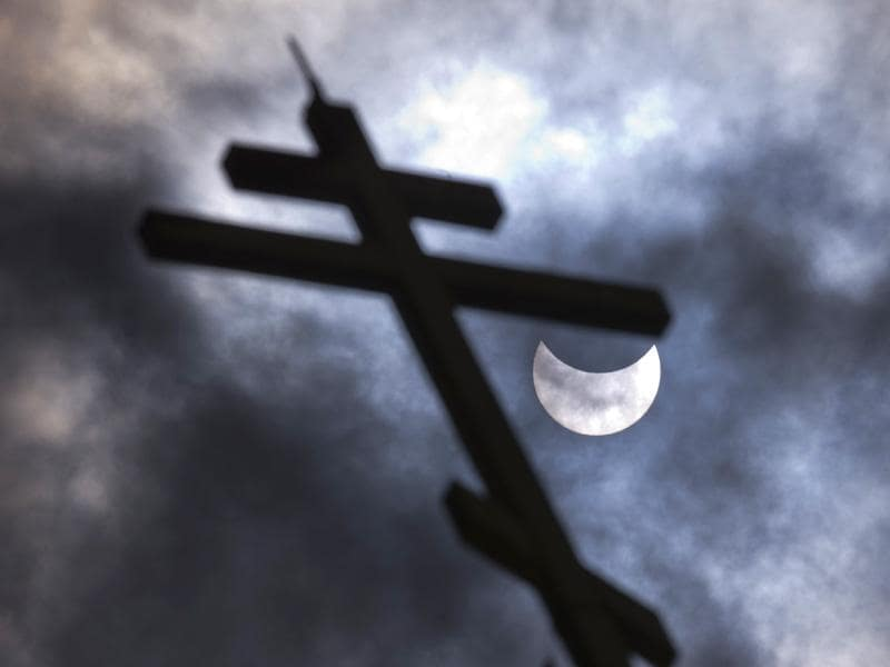 A picture taken on March 20, 2015 shows a partial solar eclipse of the sun behind a cross on the Church of St Nicholay in Sofia. (AFP Photo)