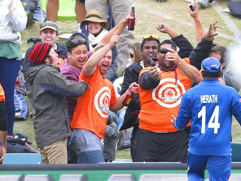 A spectator in the crowd celebrates after taking a catch off six runs hit by New Zealand batsman Kane Williamson during their Cricket World Cup match against Sri Lanka in Christchurch, February 14, 2015. REUTERS