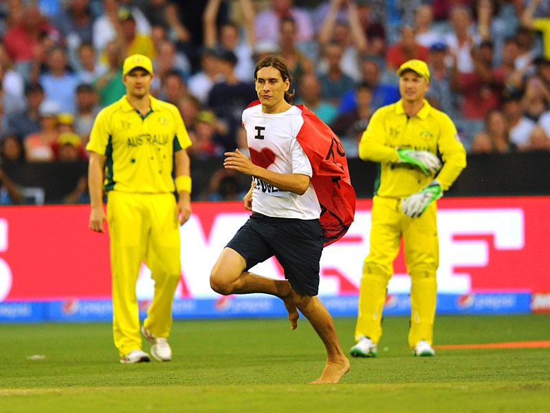 A protester wearing a shirt with the slogan 'I love Refugees' written on it, ran onto the field during the Pool A match between Australia and England at the Melbourne Cricket Ground (MCG) February 14, 2015. REUTERS